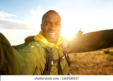 Portrait of happy young black man hiking with backpack taking selfie and pointing to sunset