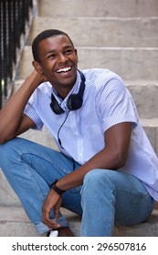 Portrait of a happy young black man sitting on steps with headphones
