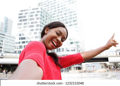 Portrait of happy young black woman taking selfie in the city and pointing to buildings