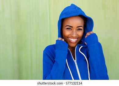 Portrait of happy young black woman smiling against green wall