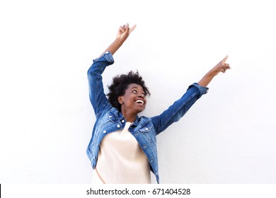 Portrait of happy young black woman pointing up against white background