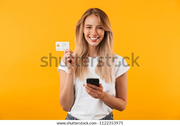 Portrait of a happy young blonde girl showing plastic credit card while holding mobile phone isolated over yellow background