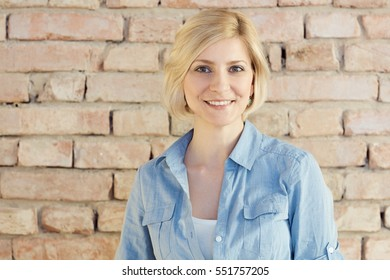 Portrait of happy young blonde woman looking at camera.