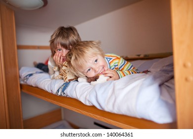 Portrait of happy young boy with brother lying on bunk bed at home