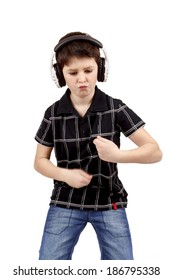 Portrait of a happy young boy listening to music on headphones and dancing against white background