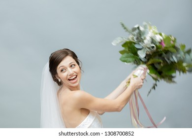 Portrait of a Happy Young Bride Throwing a Bouquet
