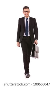 Portrait of a happy young business man carrying a suitcase, walking on white background
