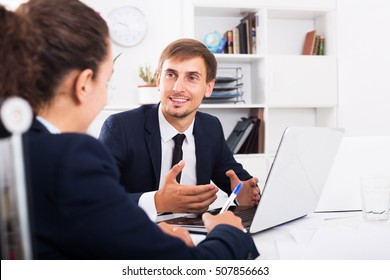 Portrait of happy young business man sitting with laptop on desk in office on working day