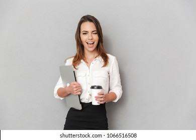 Portrait of a happy young business woman holding laptop computer and cup of coffee to go isolated over white background