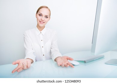 Portrait of a happy young business woman shows her open hands in welcome gesture over the office