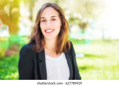 Portrait of a happy young business woman wearing a black jacket and white shirt. A female model with smooth, perfect skin. A blurred sunny and colorful background. Space for copy.