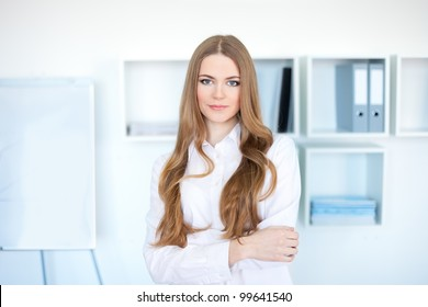 Portrait of happy young business woman standing in office