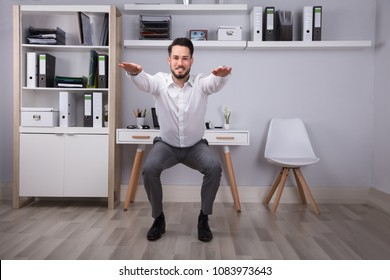 Portrait Of A Happy Young Businessman Doing Workout In Office