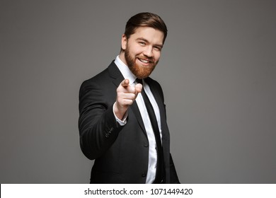 Portrait of a happy young businessman dressed in suit pointing finger at camera isolated over gray background
