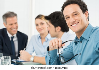 Portrait Of Happy Young Businessman Looking At Camera In Front Of His Colleague