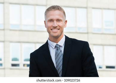 Portrait Of A Happy Young Businessman Outside