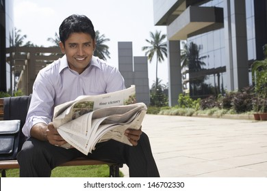 Portrait of happy young businessman reading newspaper outdoors