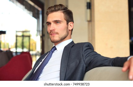 Portrait of happy young businessman sitting on sofa in hotel lobby