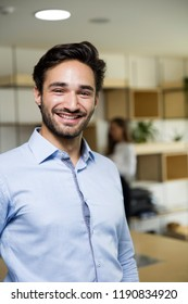 Portrait of happy young businessman smiling at the office