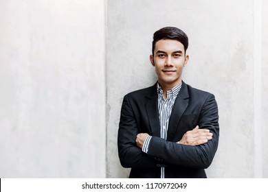 Portrait of Happy Young Businessman standing at the Wall, Smiling and Crossed Arms, Looking at camera