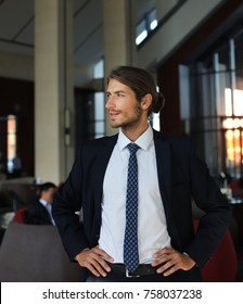 Portrait of happy young businessman standing in hotel lobby