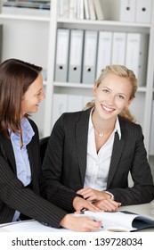 Portrait of happy young businesswoman with female coworker at desk in office