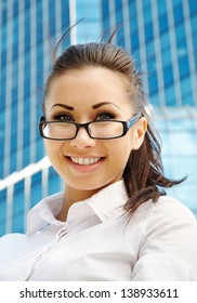 Portrait of happy young businesswoman with glasses over office building
