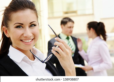 Portrait of happy young businesswoman with glasses on background her colleagues