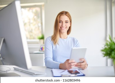Portrait of happy young businesswoman holding digital tablet in her hands and working while sitting at office desk in front of laptop.