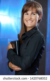 Portrait of happy young businesswoman holding personal organizer, smiling.