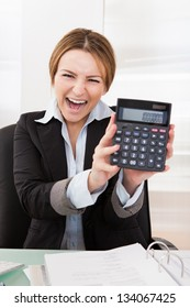 Portrait Of Happy Young Businesswoman Showing Calculator
