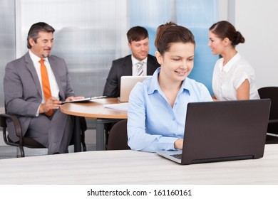 Portrait Of A Happy Young Businesswoman Using Laptop At Desk In Office