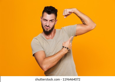 Portrait of a happy young casual man standing isolated over orange background, pointing at his bicep