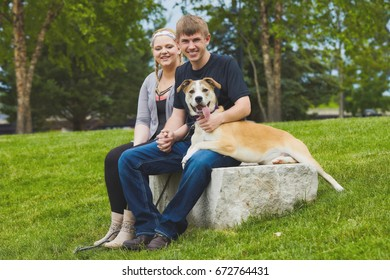 Portrait of happy young Caucasian couple sitting together on stone holding their dog, looking at camera and smiling in park