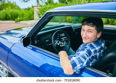 Portrait of happy young Caucasian man wearing checked shirt driving blue car, looking at camera and smiling
