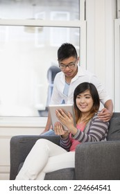 Portrait of happy young Chinese Couple relaxing at home.