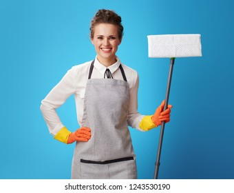 Portrait of happy young cleaning lady in apron with mop against blue background. Professional woman cleaner will provide a simple and hassle-free service