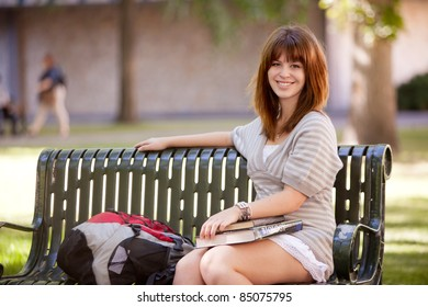 Portrait of a happy young college girl outdoors on a bench
