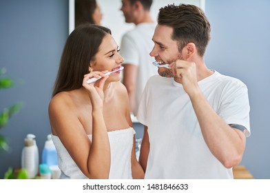 Portrait of happy young couple brushing teeth in the bathroom