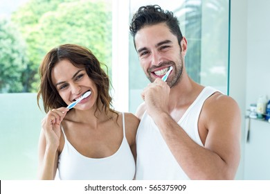 Portrait of happy young couple brushing teeth in bathroom