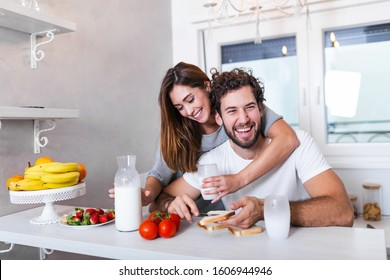 Portrait of happy young couple cooking together in the kitchen at home. Cute young couple enjoying their breakfast together she is pouring him milk wile