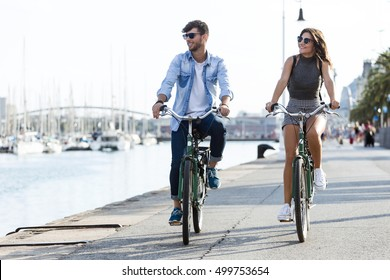 Portrait of happy young couple cycling in the city.