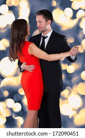 Portrait Of Happy Young Couple Dancing On Bokeh Background