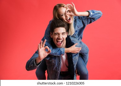 Portrait of a happy young couple dressed in denim jackets standing together isolated over red background, piggyback ride, showing ok gesture