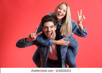 Portrait of a happy young couple dressed in denim jackets standing together isolated over red background, piggyback ride, showing peace