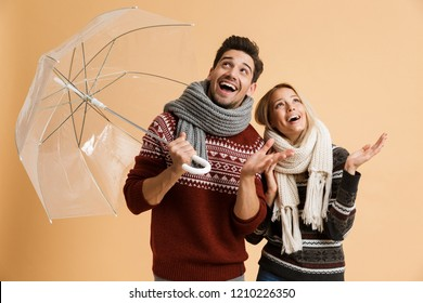 Portrait of a happy young couple dressed in sweaters and scarves standing together isolated over beige background, holding umbrella