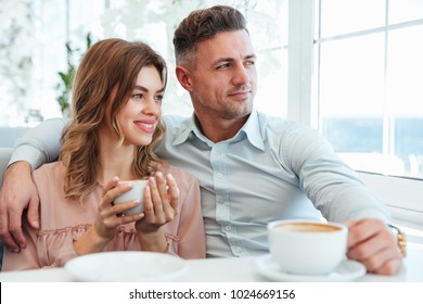 Portrait of a happy young couple drinking coffee while sitting together at the cafe table indoors