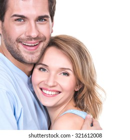 Portrait of happy young couple in embrace standing on white background.
