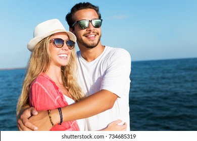 Portrait of happy young couple enjoying the day on the beach.