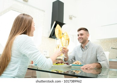 Portrait of happy young couple having diner together in modern kitchen and clinking champagne glasses sitting at glass table